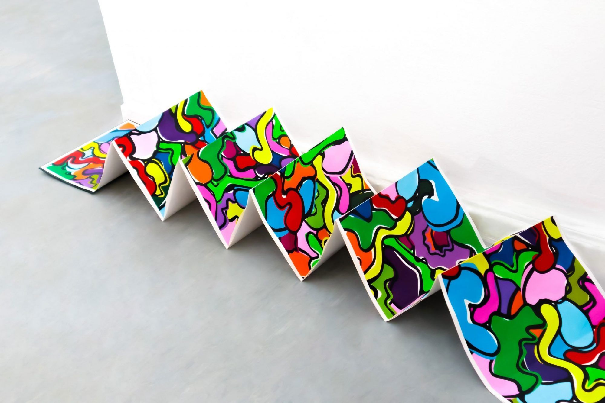 A very long concertinaed page covered in brightly coloured organic shapes and outlined in black is opened out across a grey floor. The end lies flat on the floor with the rest of the page standing on points of the zig-zag. It stands next to a white wall.