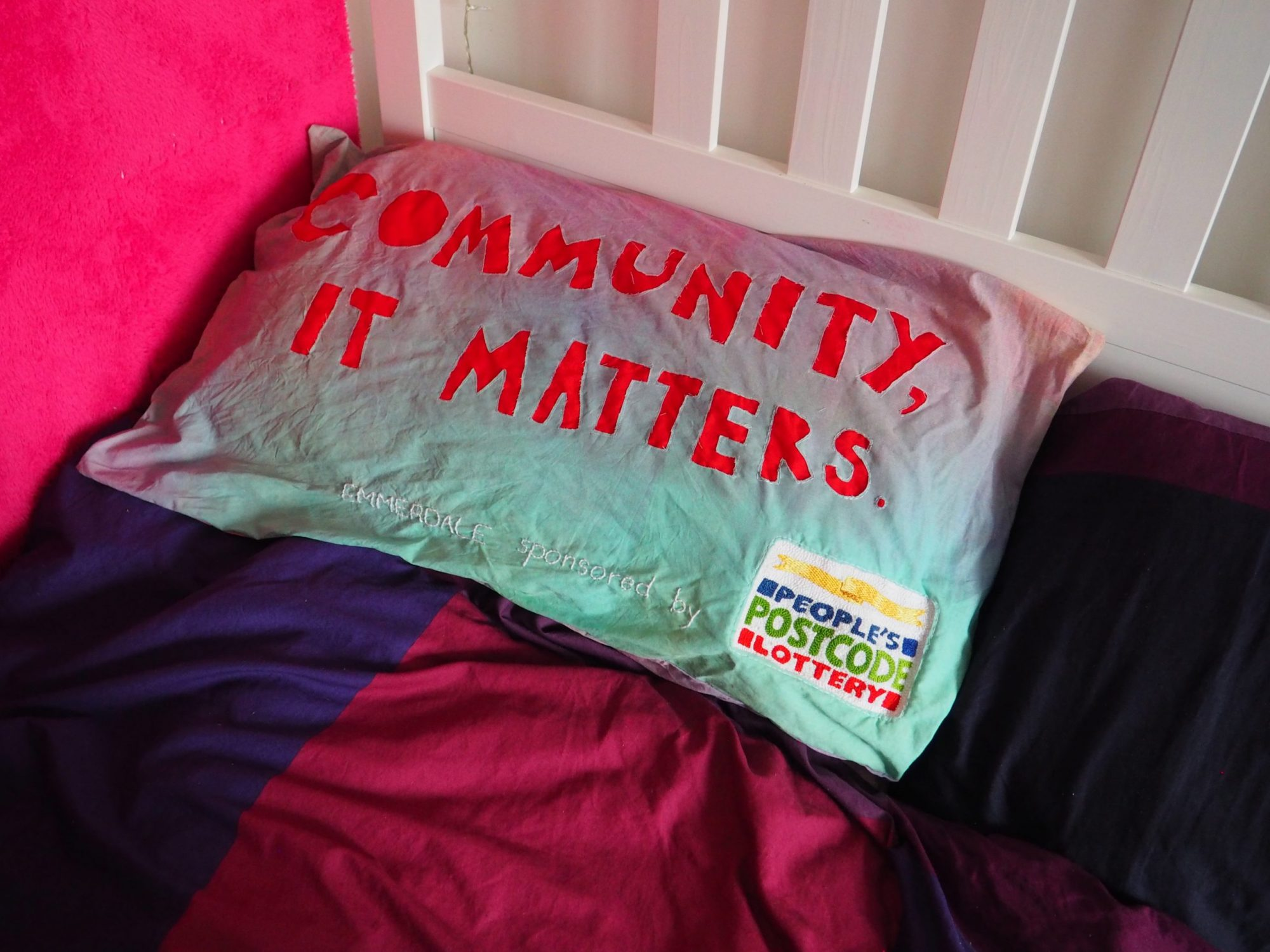"""Placed on a bed with a white headboard is a pillow dyed with a fade of green to pink with the words: """"COMMUNITY, IT MATTERS"""" in large letters on the front in red fabric. The wall to the left is bright pink and the bed sheets are dark purples and blues. Below embroidered in white thread are the words: """"EMMERDALE sponsored by"""" next to a very fine detailed embroidered logo of: """"People's Postcode Lottery""""."""