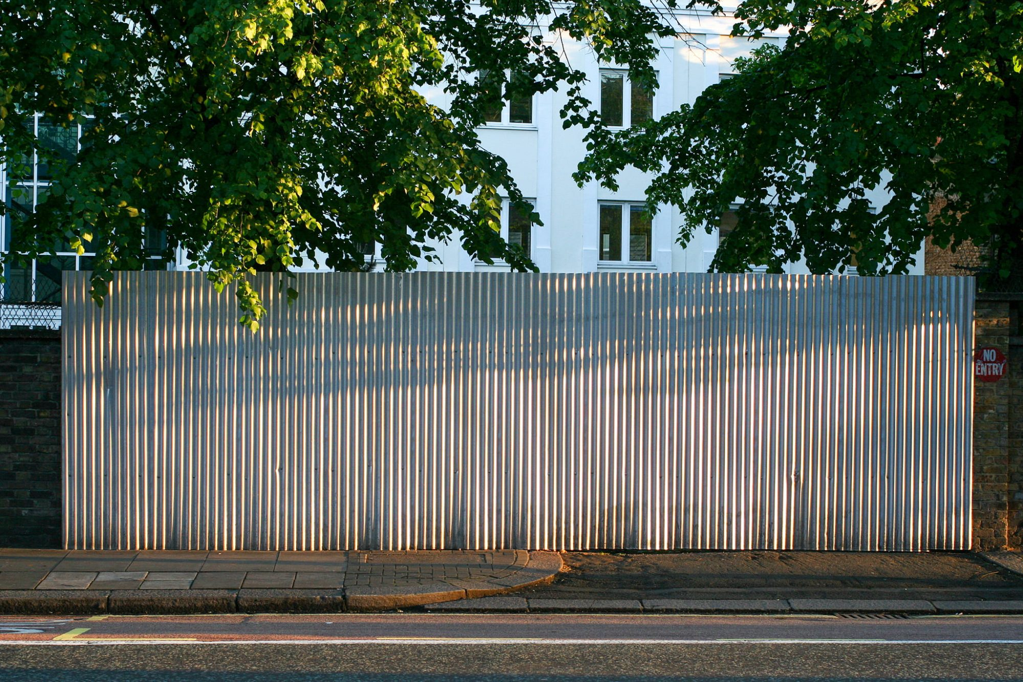 Parallel to the road, lining the pavement, is a tall corrugated sheet of metal standing on end. It fills the image. The road is just visible at the bottom of the image with a building and trees behind the sheet metal. A small no entry sign in red and white is on the wall to the right of the metal.