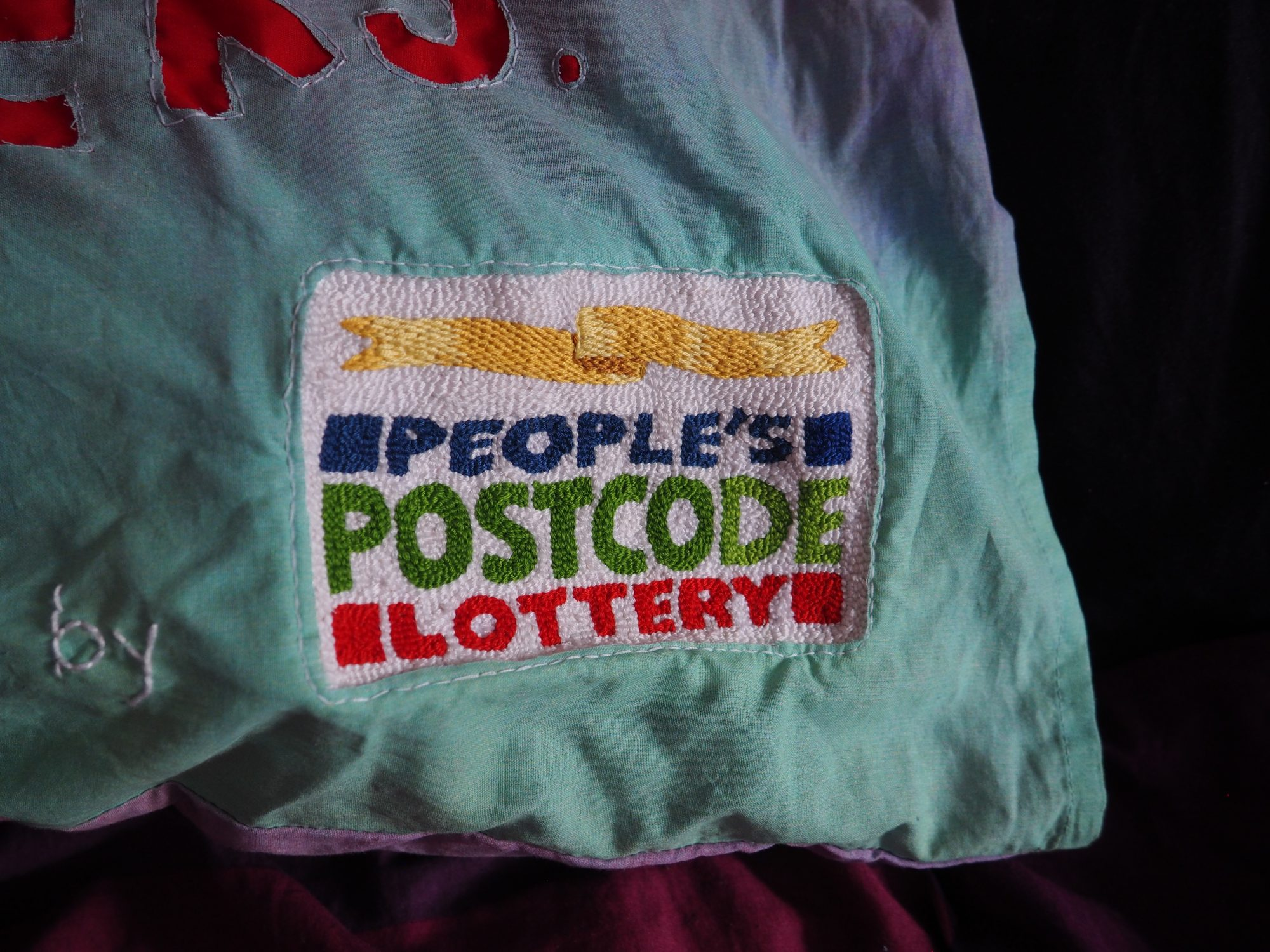 On a dark purple sheet of fabric is the corner of a pillow dyed with a fade of green to pink. A very finely detailed embroidered logo of 'People's Postcode Lottery' covers the fabric with a fine white stitch following the edge of the logo.
