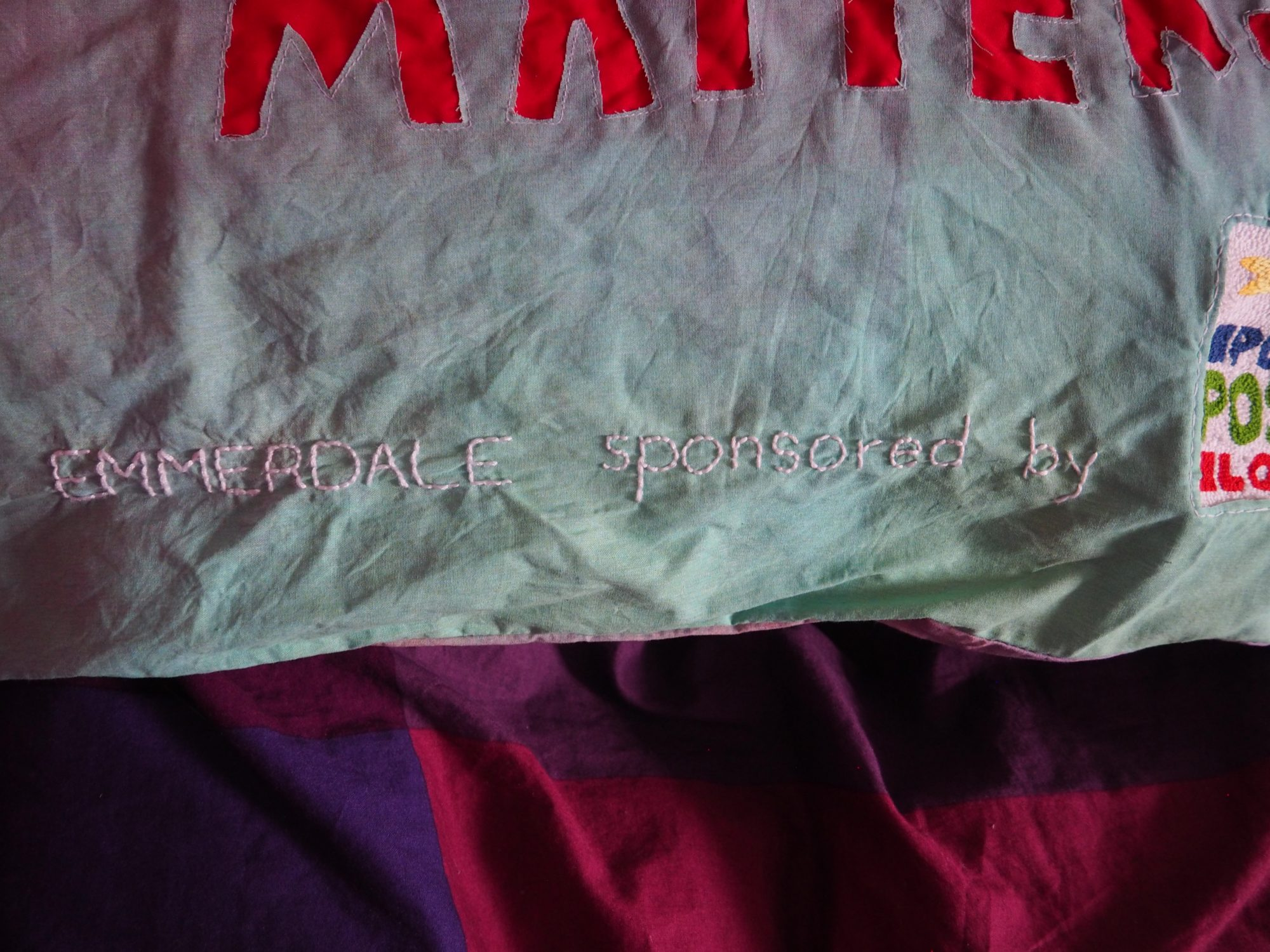 """On a sheet of darker fabric sits a section of the bottom edge of a pillow. The fabric is a pastel green and has the words: """"EMMERDALE sponsored by"""" in thick white embroidery thread."""
