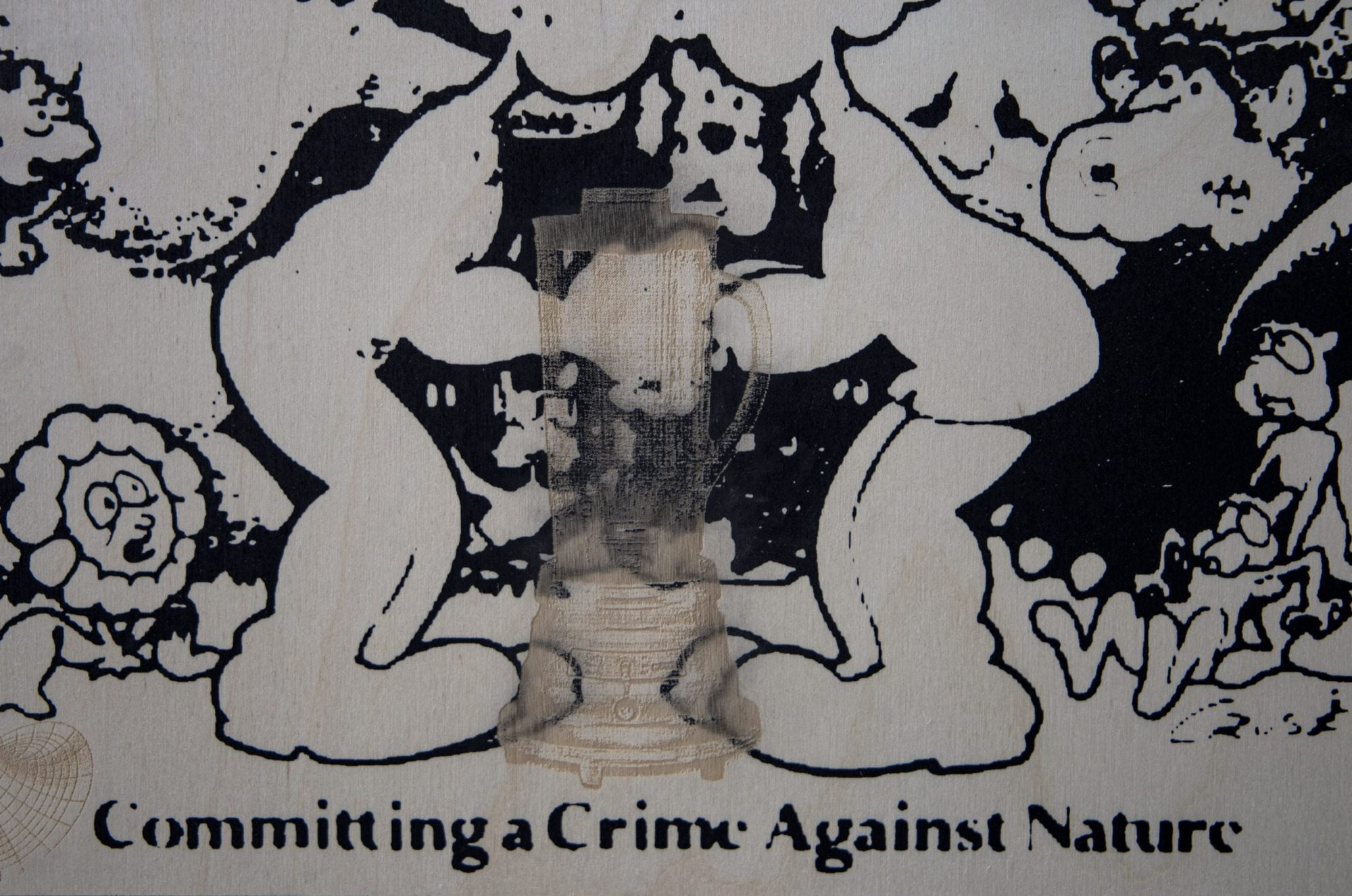 """A faint and slightly see-through outline of a blender sits central to the image. In the background are crowded black printed images of indistinct cartoon characters. Two identical figures face each other in the centre, joined partially in a kiss, although the tops of their heads are cropped off. Along the bottom, black stencil-like text reads: """"Committing a Crime Against Nature"""""""