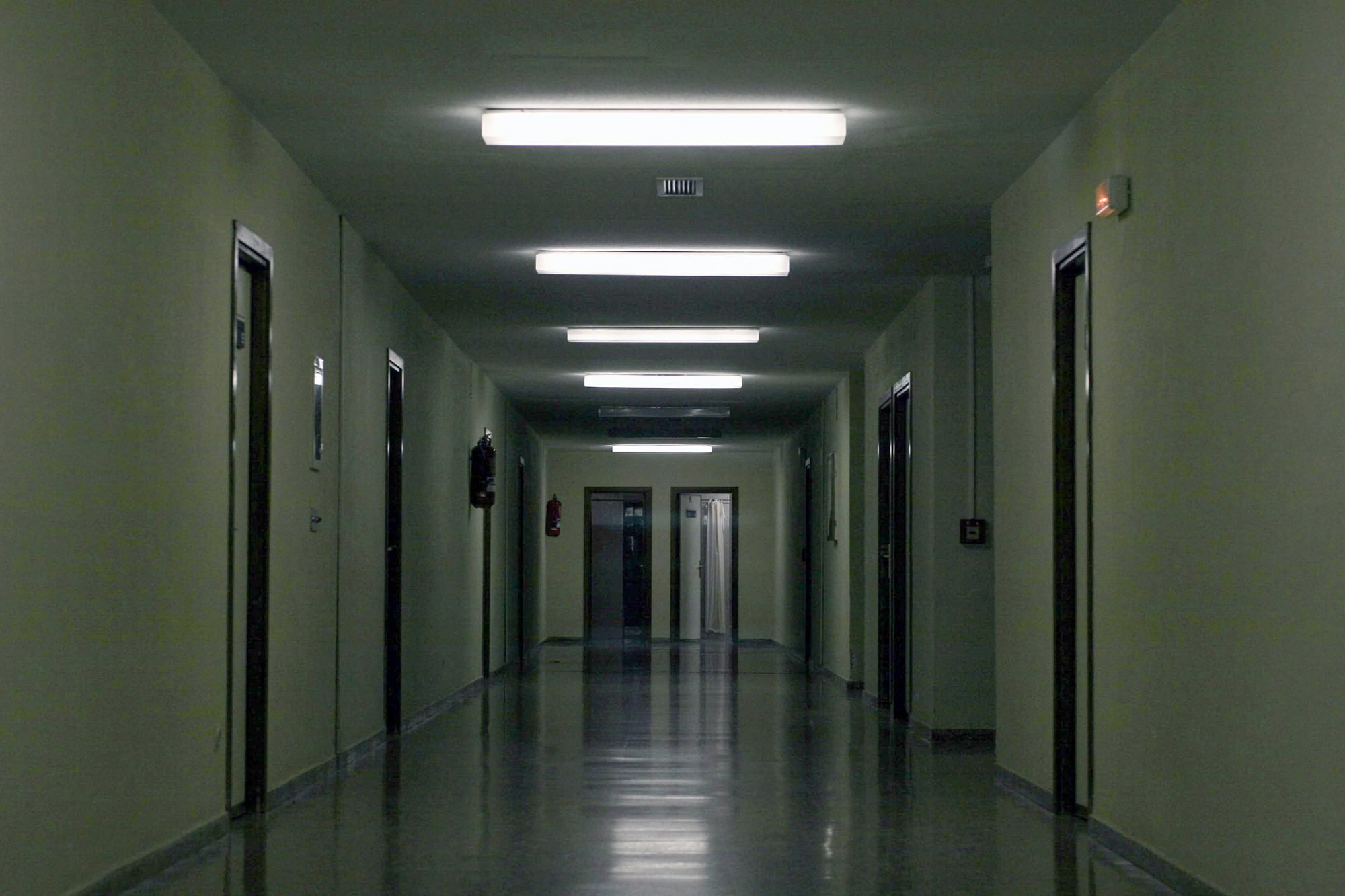 An empty gloomy corridor is lit by long ceiling lights overhead. Down both sides are multiple doorways with two open doors at the end of the corridor.