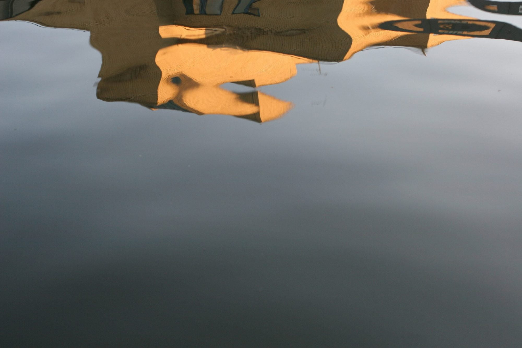 An expanse of water fills the image. At the top of the image is a distorted reflection of a building in pale brick. The water is very still.